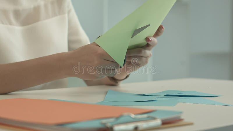 A mulher está cortando o papel verde usando tesouras fotos de stock