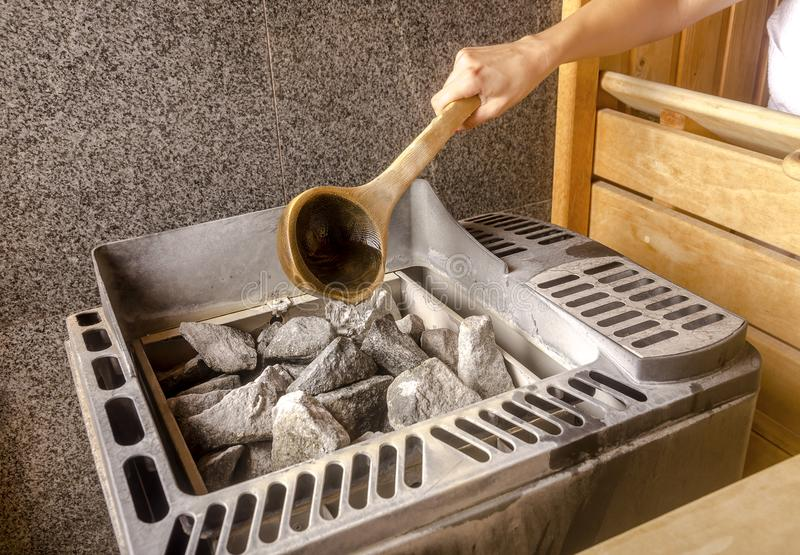 A mulher está derramando a água na pedra quente na sala dos termas da sauna foto de stock