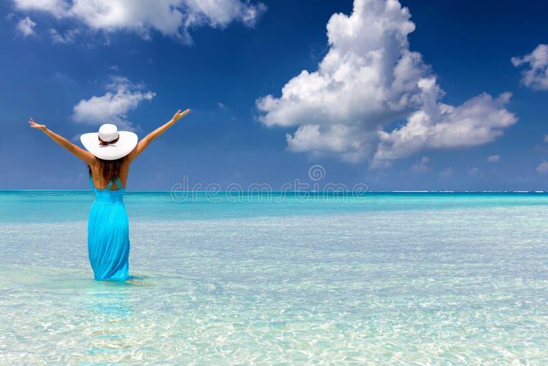 A mulher está em tropical, a turquesa molha e aprecia suas férias imagem de stock royalty free