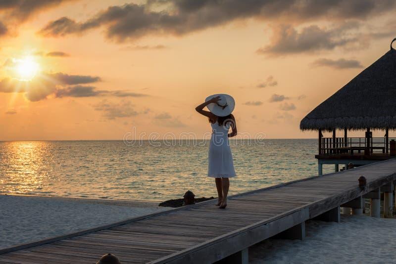 A mulher está em um molhe de madeira nos maldives fotografia de stock