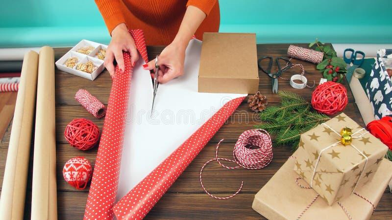 A mulher está a empacotar presentes, vista superior na área de trabalho Preparando-se para o Natal foto de stock