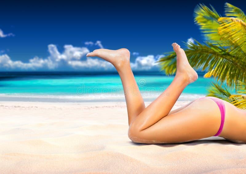 A mulher está encontrando-se na praia tropical foto de stock
