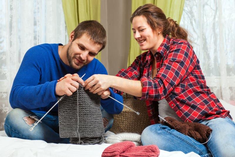 A mulher está ensinando a malha um homem novo imagens de stock royalty free