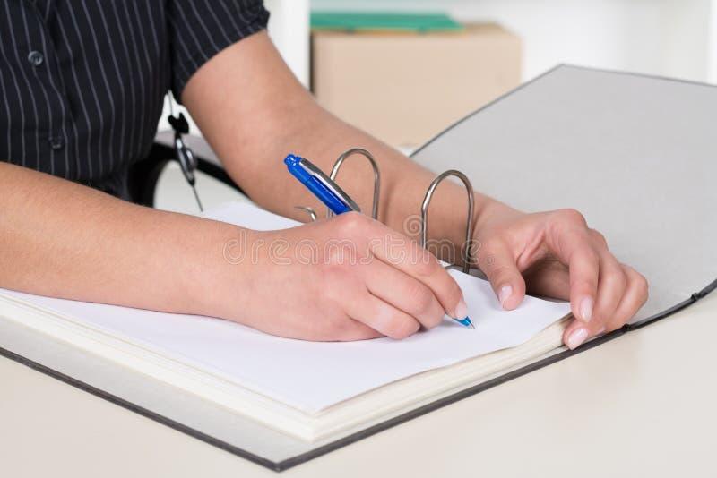 A mulher está escrevendo em um arquivo fotografia de stock royalty free