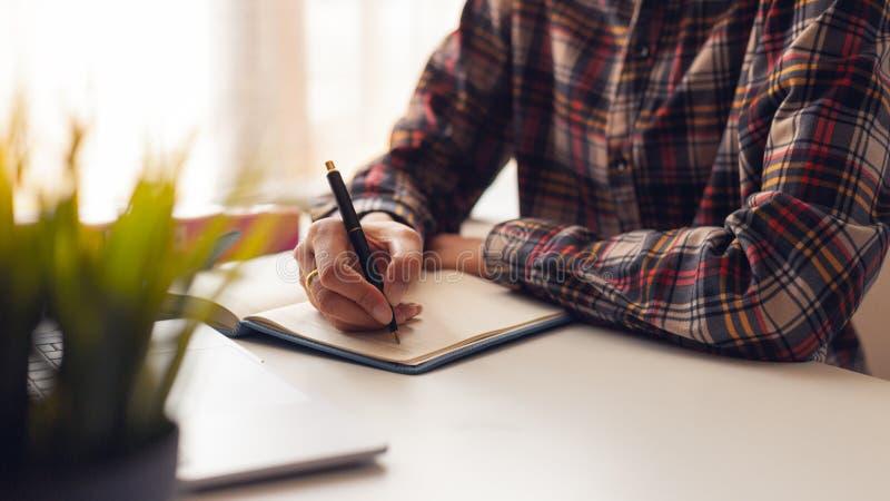 A mulher está escrevendo uma mensagem no livro na tabela foto de stock