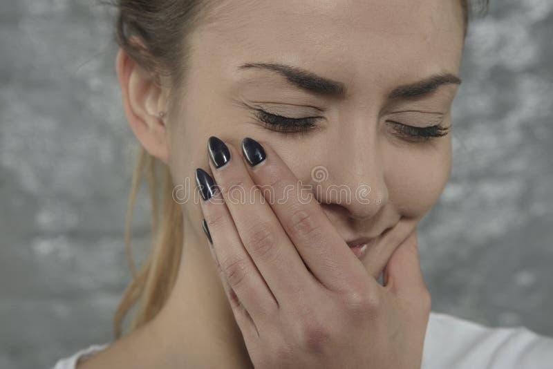 A mulher está esforçando-se com a dor de dente, mão no mordente fotos de stock