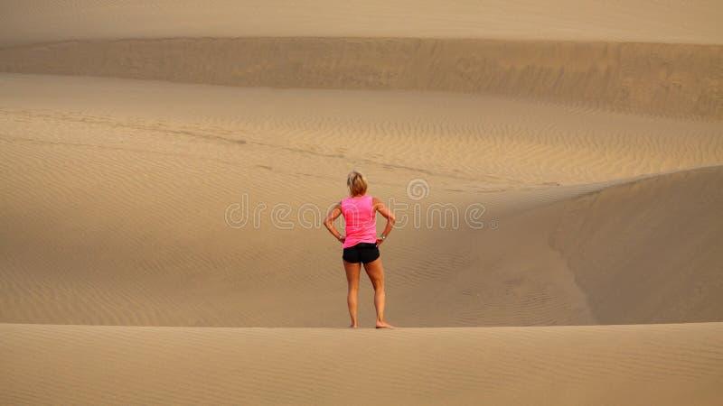 A mulher está estando o deserto da areia de Maspalomas foto de stock
