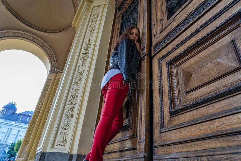 A mulher está estando perto da porta de madeira grande na construção do estilo antigo da academia Ângulo da fotografia de baixo d foto de stock royalty free