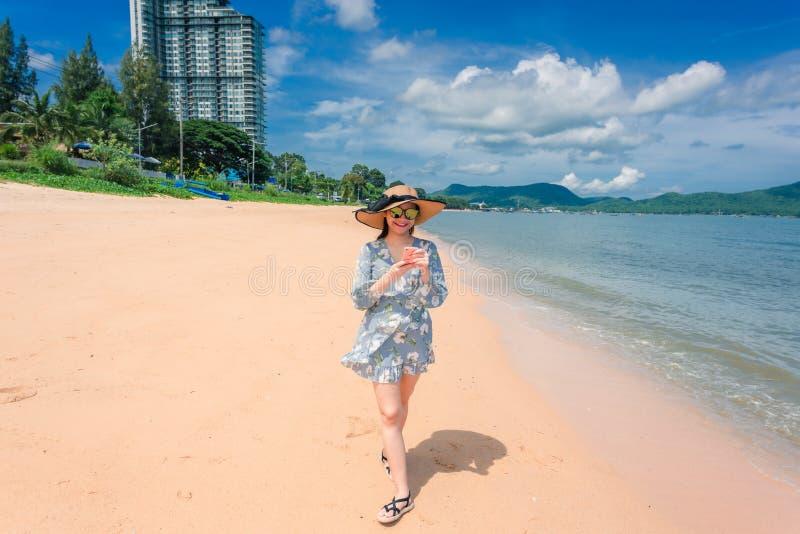 A mulher está feliz e dá uma volta em umas férias da praia foto de stock