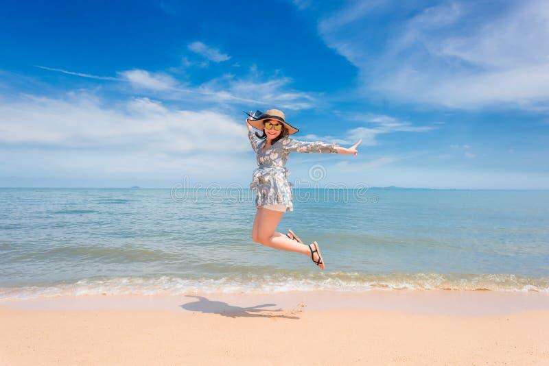 A mulher está feliz e salta em seu feriado imagem de stock