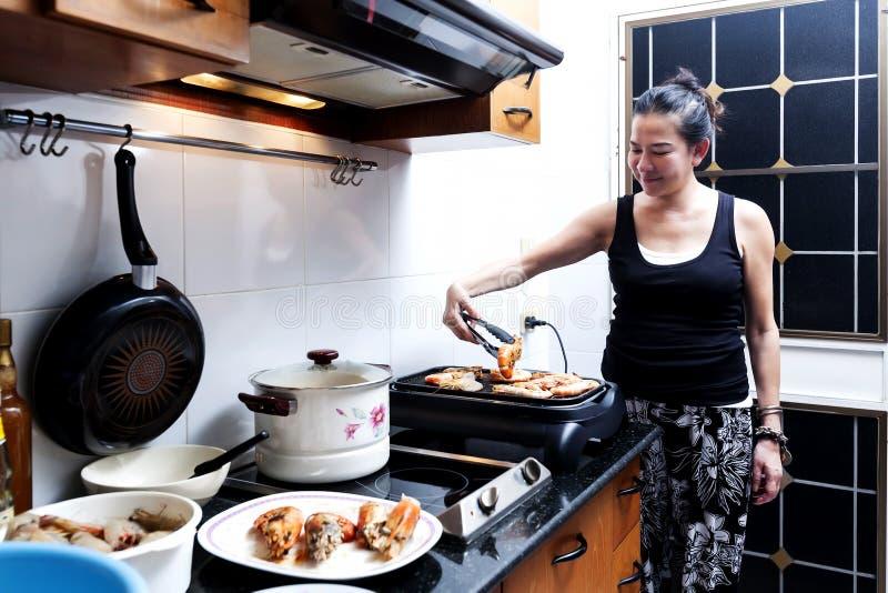 A mulher está grelhando o camarão imagem de stock