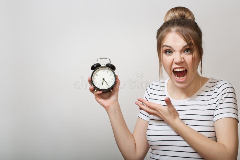 A mulher está gritando Mulher que guarda um despertador imagens de stock