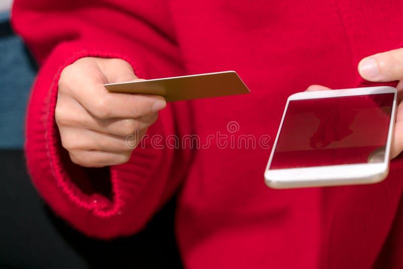 A mulher está guardando o cartão de crédito para a compra em linha para o presente do ano novo da família imagem de stock royalty free