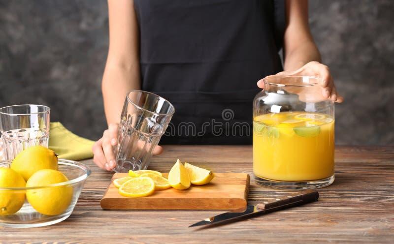 A mulher está indo derramar o suco de limão fresco no vidro na tabela fotos de stock