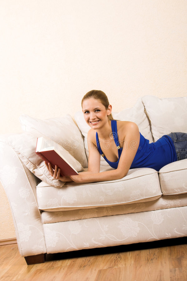 A mulher está lendo em uma sala de estar imagem de stock royalty free