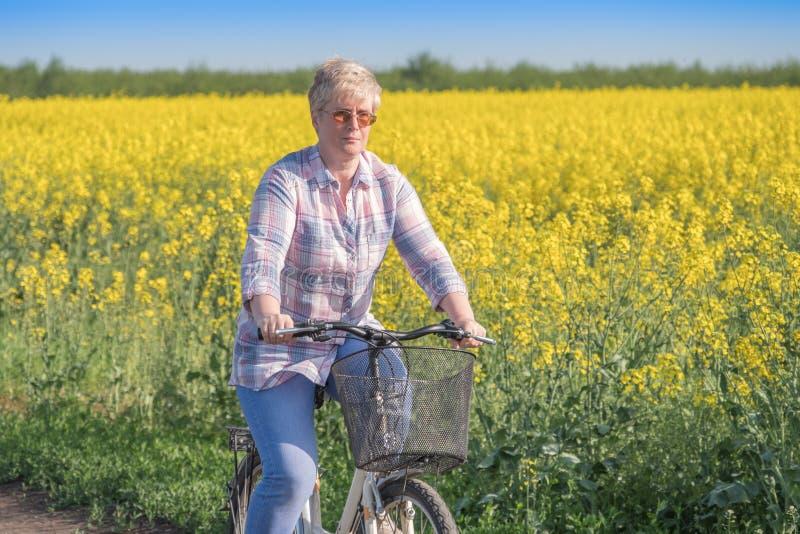 A mulher está montando uma bicicleta imagem de stock royalty free