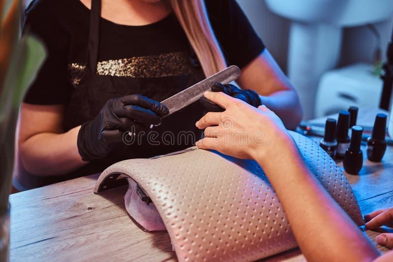 A mulher está obtendo um tratamento de mãos do prego O mestre do prego está arquivando pregos a um cliente imagem de stock royalty free