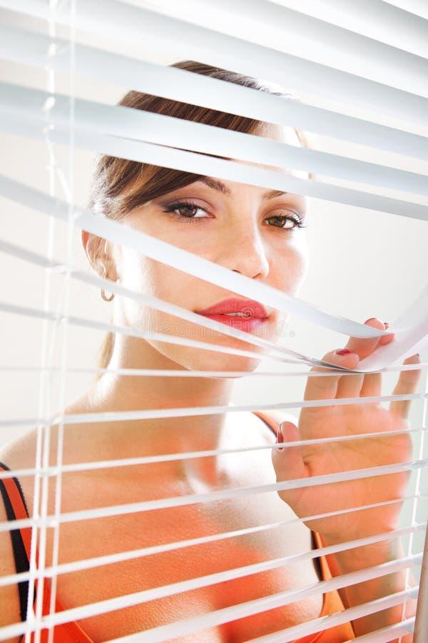 A mulher está olhando através do jalousie l fotos de stock royalty free