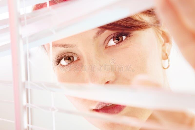 A mulher está olhando com a manutenção programada do jalousie fotos de stock royalty free
