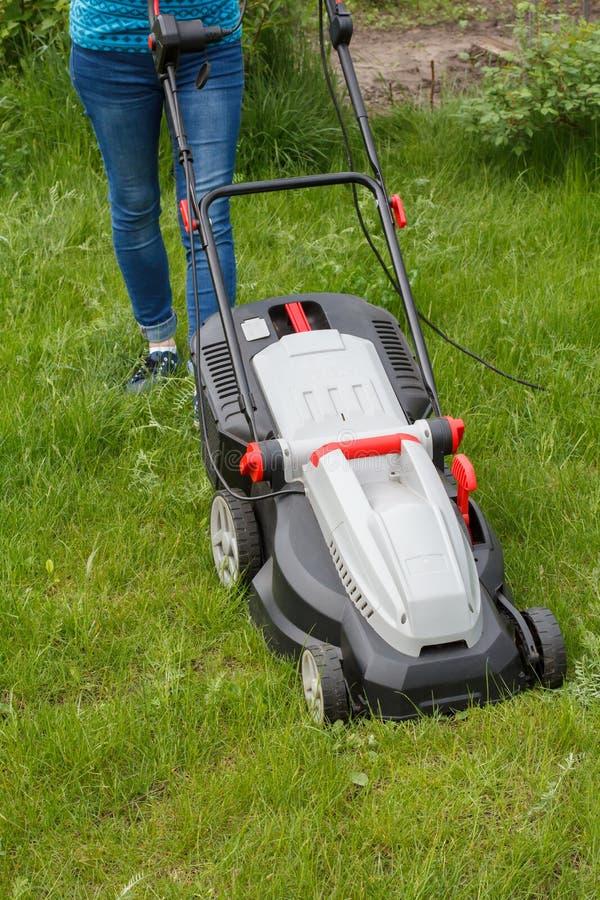 A mulher est? operando-se com o cortador de grama no jardim fotos de stock royalty free