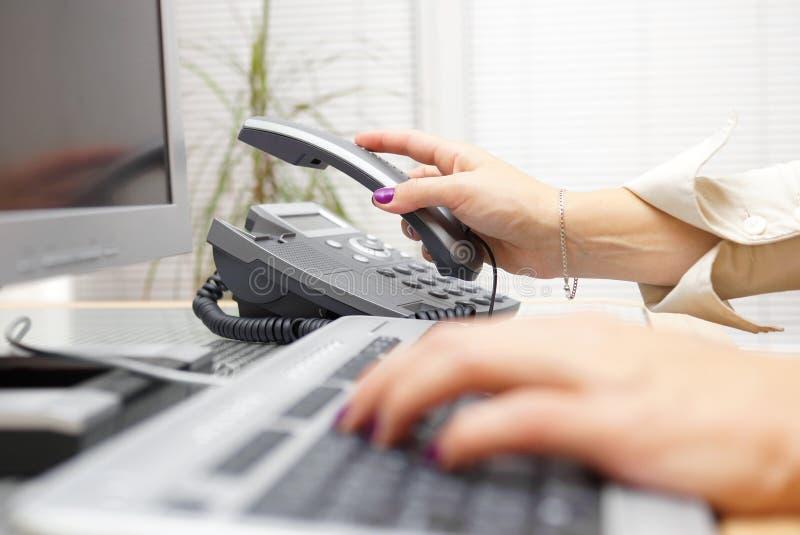 A mulher está pegarando os auriculares do telefone, conceito do auxílio imagem de stock