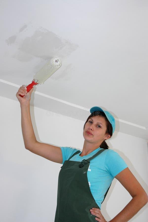 A mulher está pintando o teto imagem de stock royalty free