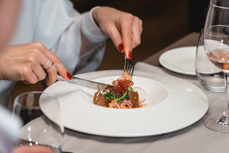 A mulher está preparando-se para comer a salada salmon deliciosa em um restaurante parcela pequena foto de stock