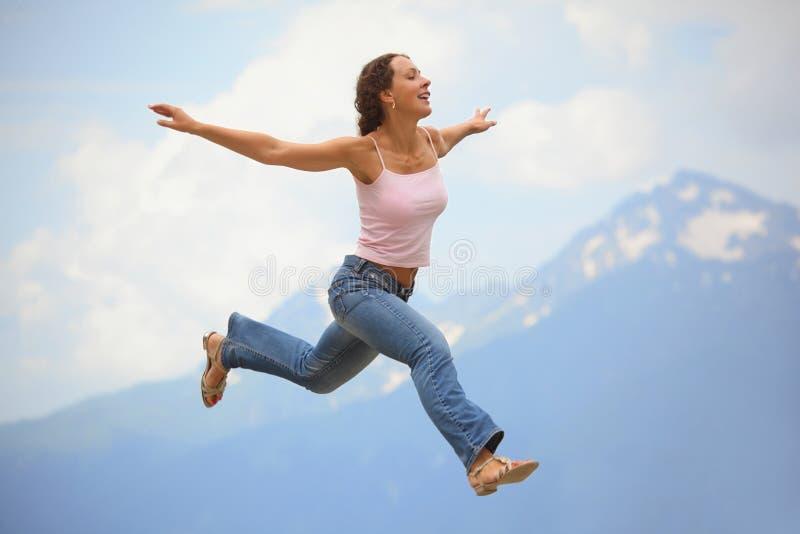 A mulher está saltando com o separado largo das mãos imagem de stock royalty free
