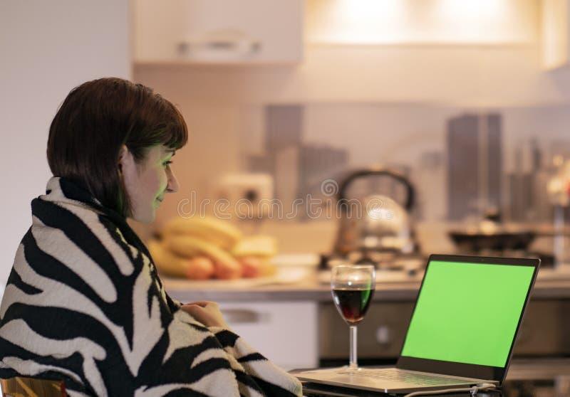 A mulher está sentando-se na cozinha na tabela pelo portátil e com um sorriso olha a tela de monitor, chromakey foto de stock