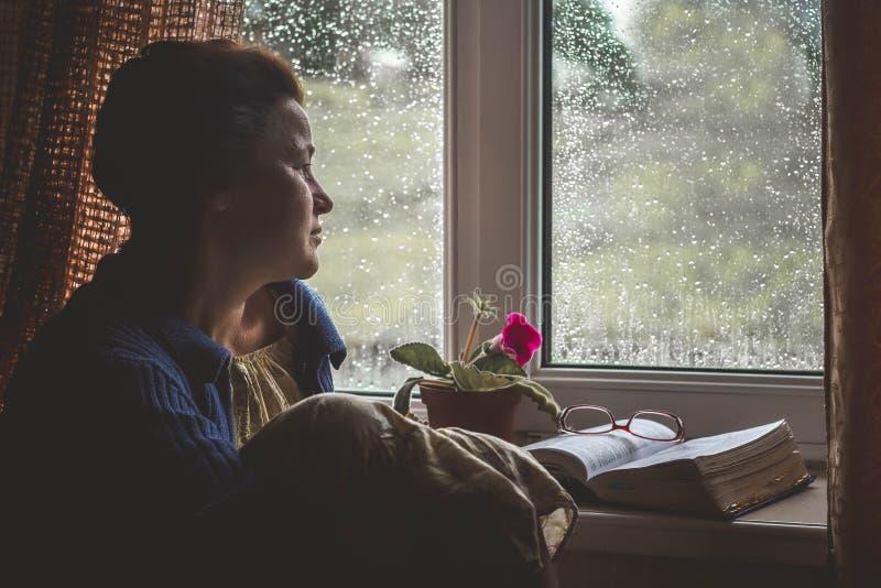 A mulher está sentando-se pela janela com livro distribuído, é pensar imagens de stock