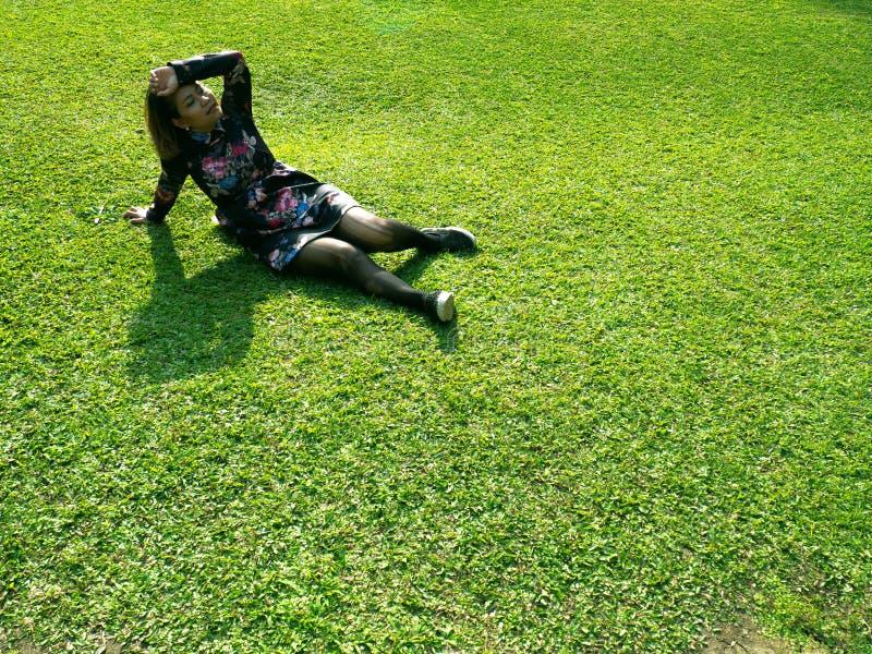 A mulher está sentindo virada A menina está sentando-se na pastagem verde A fêmea está vestindo flores e o vestido preto fotografia de stock