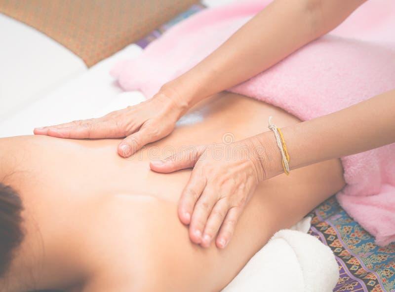 A mulher está tendo a massagem traseira nos termas imagens de stock