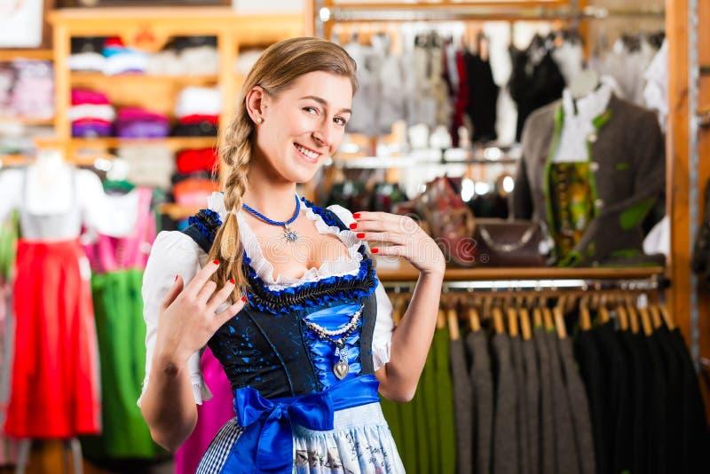 A mulher está tentando Tracht ou dirndl em uma loja fotografia de stock royalty free