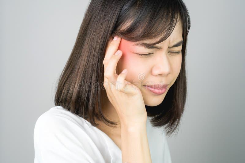 A mulher está tocando em sua cabeça para mostrar sua dor de cabeça As causas podem ser causadas pelo esforço ou pela enxaqueca Ou imagens de stock royalty free