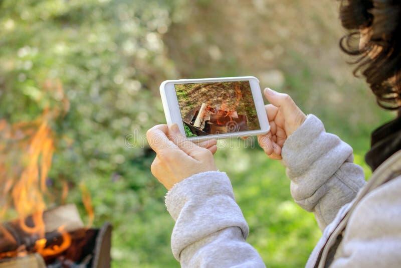 A mulher está tomando imagens do fogo em seu smartphone outdoors fotos de stock royalty free