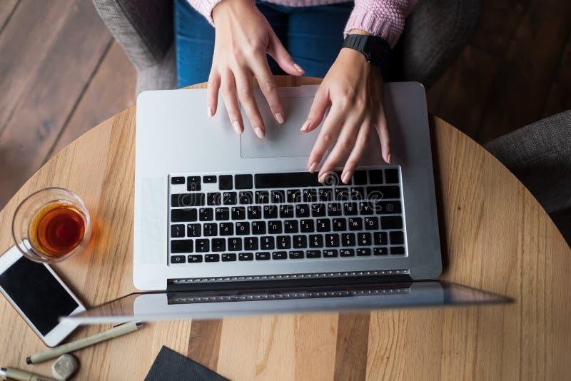 A mulher está trabalhando usando um laptop na tabela de madeira Mãos que datilografam em um teclado imagens de stock