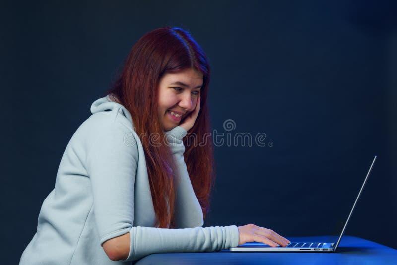 A mulher está usando o portátil para uma comunicação no bate-papo ou no bate-papo video Conceito social dos media fotografia de stock royalty free