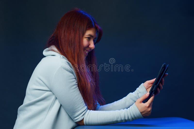 A mulher está usando o tablet pc para uma comunicação no bate-papo ou no bate-papo video Conceito social dos media imagens de stock