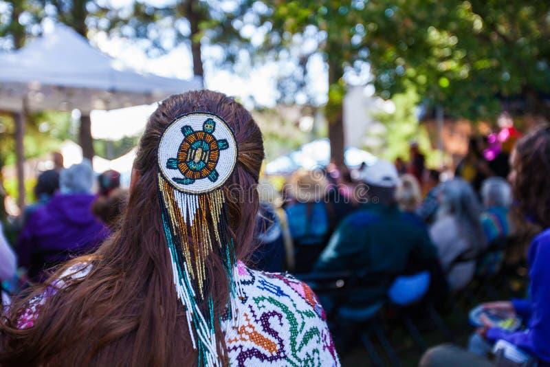 A mulher está vestindo um pino de cabelo frisado da grande tartaruga e uma roupa nativa colorida imagens de stock