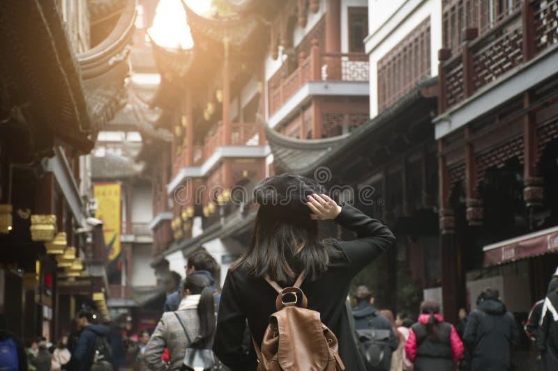 A mulher está viajando no marco de passeio do mercado de rua do jardim velho de Yu Yuan da cidade em Shanghai imagens de stock