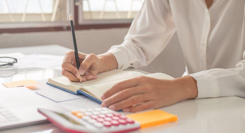 A mulher est? escrevendo uma mensagem no livro na tabela fotografia de stock royalty free