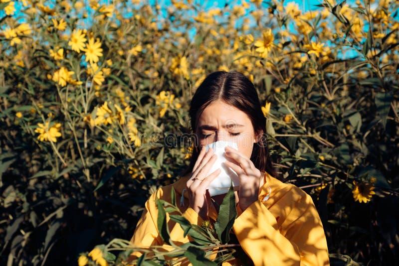 A mulher est? fundindo seu nariz perto das flores na flor Mo?a que espirra e que guarda o tecido de papel em umas m?o e flor fotografia de stock royalty free