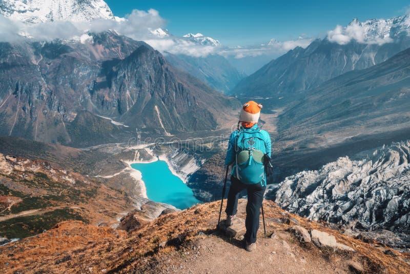 Mulher estando com a trouxa no pico de montanha fotografia de stock royalty free