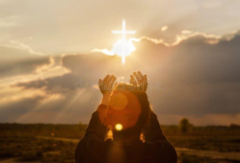 A mulher estende sua mão à cruz fotografia de stock