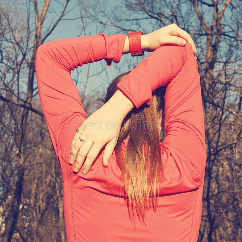 A mulher estica seus parte superior do corpo e braços antes de excercising fotos de stock