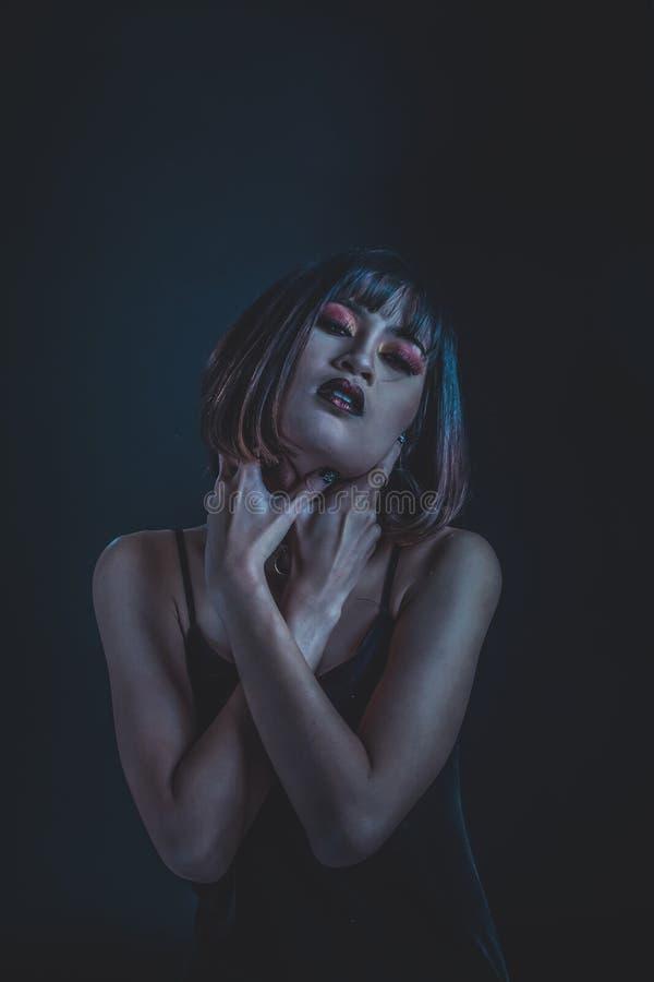 Mulher estranha com maquiagem de tom escuro sobre fundo preto, fotografia de retrato imagem de stock