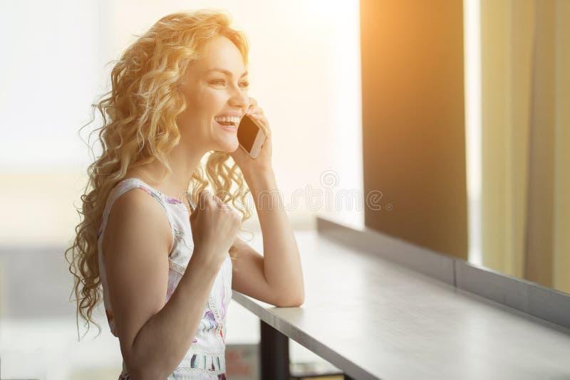 Mulher eufórico que procura o trabalho no café A menina bonita está falando no telefone e feliz com a boa notícia imagem de stock royalty free