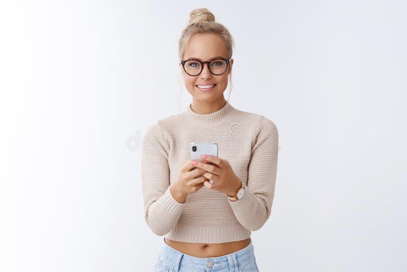 A mulher europeia atrativa de encantamento com penteado do bolo nos vidros que mantêm o sorriso do smartphone otimista e otimista fotos de stock royalty free