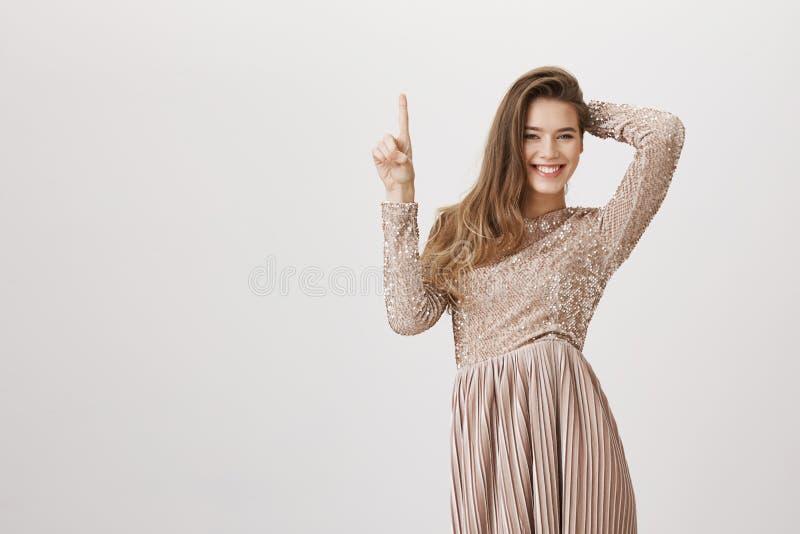 Mulher europeia atrativa no vestido de noite bege encantador que aponta acima ao guardar a mão na cabeça, sorrindo amplamente em foto de stock royalty free