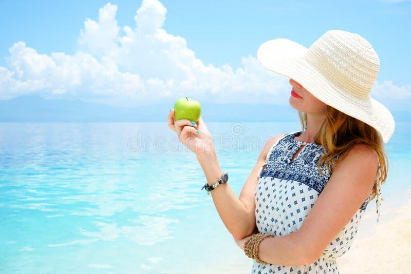 A mulher europeia bonita nova está mantendo a maçã verde em sua mão contra o mar tropical macio calmo sob o azul macio imagem de stock